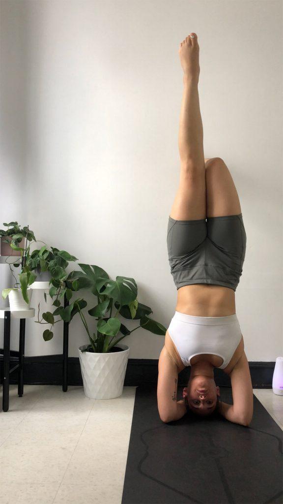 Karen practicing a yoga headstand.